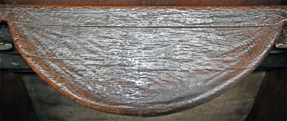 Misericord seat showing three clear sections of laminate.
